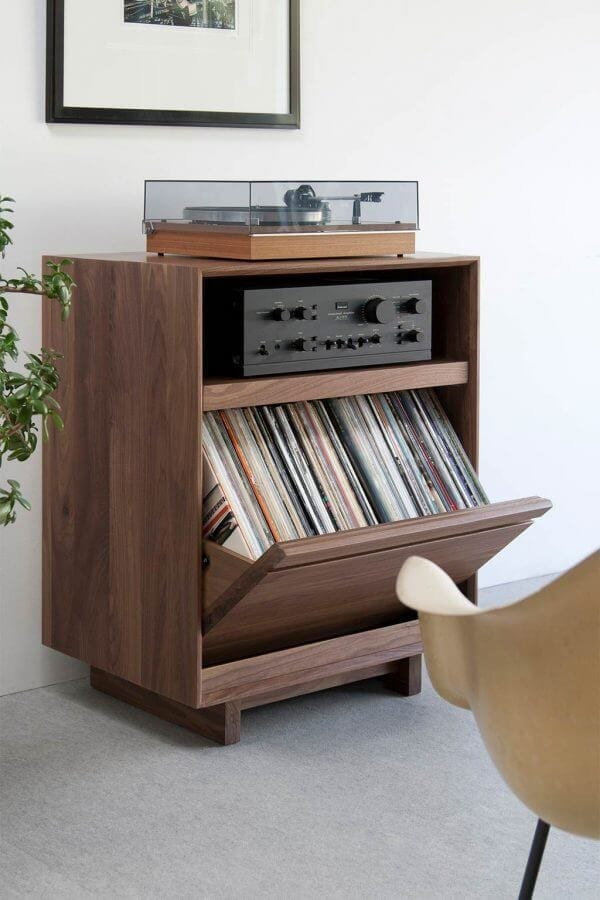 AERO 25.5 LP Storage Console made from North American hardwood. Features 1 flip-style record storage bin with room for 120 LPs. It features a Walnut finish and a Modern Record Player sits on top. The storage cabinet is sitting in a living room setting.