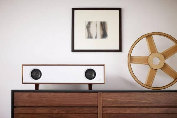 Tabletop Hifi speaker with a glacier white finish. Crafted with North American hardwoods. It sits at 28.75 inches wide and 9.5 inches tall and weighs 30 lbs. It is displayed on a living room cabinet.