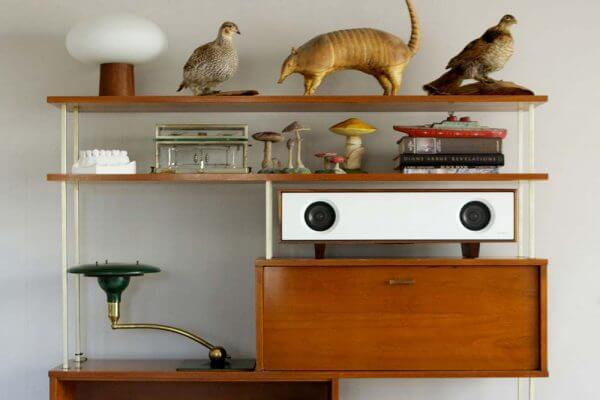 Tabletop Hifi speaker with a dark natural walnut finish. Crafted with North American hardwoods. It sits at 28.75 inches wide and 9.5 inches tall and weighs 30 lbs. It is displayed on a living space shelf with many ornaments.