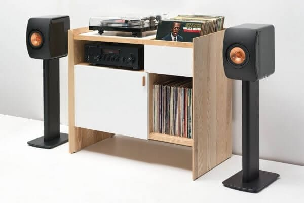 Unison Ash Record Stand with KEF and Yamaha with flip-style LP storage bins, vibration isolated record player platform, and audio cabinet room for hi-fi sound equipment. Light ash exterior and bright white paint on front-facing wood. Displayed with turntable sitting on top and standing Bluetooth powereded speakers on either side against a wall.